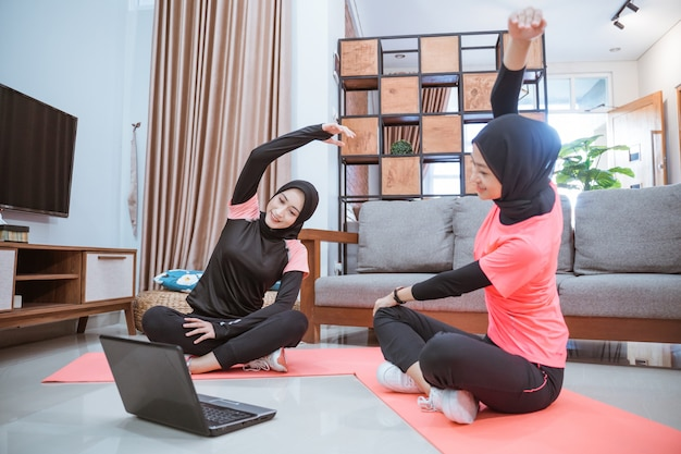 Zwei asiatische frauen, die hijab-sportbekleidung tragen, sitzen mit gekreuzten beinen auf dem boden. ihre körper sind zur seite gelehnt und die hände hoch, während sie gemeinsam ihre arme im haus aufwärmen