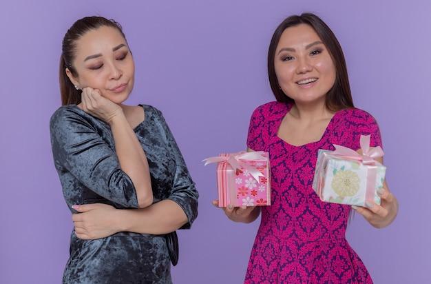 Zwei asiatische frauen, die internationalen frauentag feiern, verwirrte und beleidigte frau, die ihren besten lächelnden freund mit geschenken betrachtet, die über blauer wand stehen