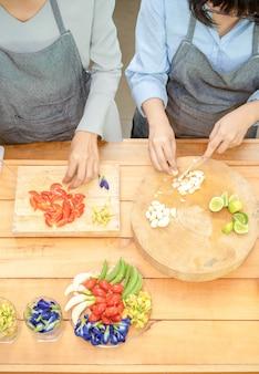 Zwei asiatische frauen schneiden knoblauch und tomate mit dem messer auf dem holzbrett mit halben limetten schlüsselblumenblume schmetterlingserbse frühlingszwiebelerbsen und eiern in diesem bereich und bereiten dann das mittagessen vor.