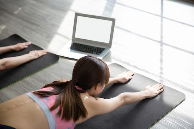 Zwei asiatische frauen suchen laptop, um yoga-training aus dem internet zu lernen