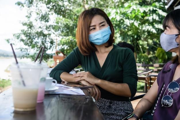Zwei asiatische freundin tragen schutzmaske im freien sprechen