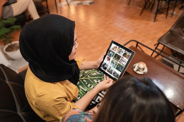 Zwei asiatische freundinnen, die tablette benutzen und einen kaffee im café trinken