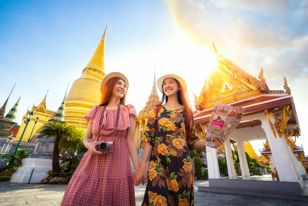 Zwei asiatische freundinnen reisen und überprüfen den standort anhand einer karte im grand palace