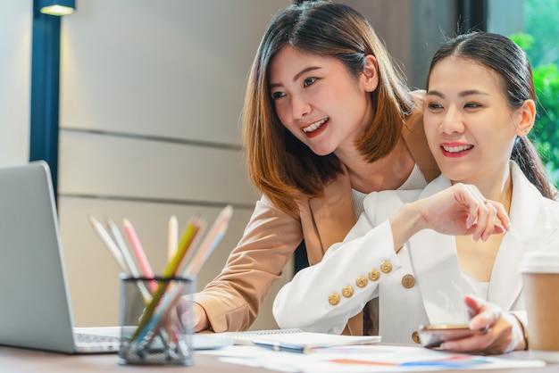 Zwei asiatische geschäftsfrauen, die mit dem partner über laptop arbeiten