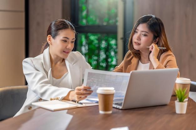 Zwei asiatische geschäftsfrauen, die mit dem partnergeschäft mit papierdiagrammdokument und technologielaptop im modernen konferenzzimmer arbeiten