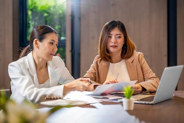 Zwei asiatische geschäftsfrauen, die mit dem partnergeschäft über technologielaptop arbeiten