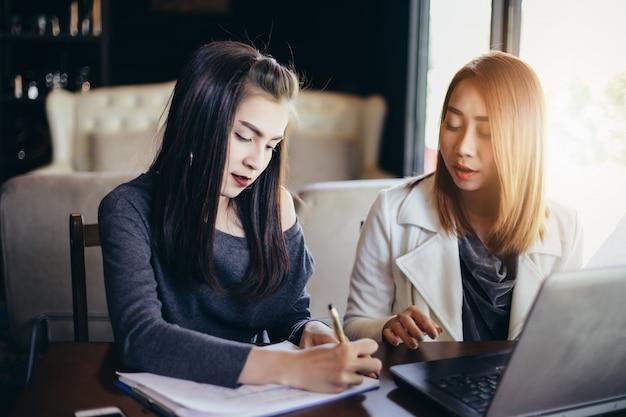 Zwei asiatische geschäftsfrauen, die notizbuchfunktion und diskussion des vertrages verwenden