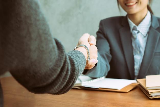 Zwei asiatische geschäftsfrauen, die rütteln, überreichen einen schreibtisch, während sie ein abkommen oder eine partnerschaft schließen
