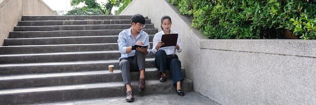 Zwei asiatische geschäftskollegen außerhalb von bürogebäuden diskutieren und kommentieren sich gegenseitig.