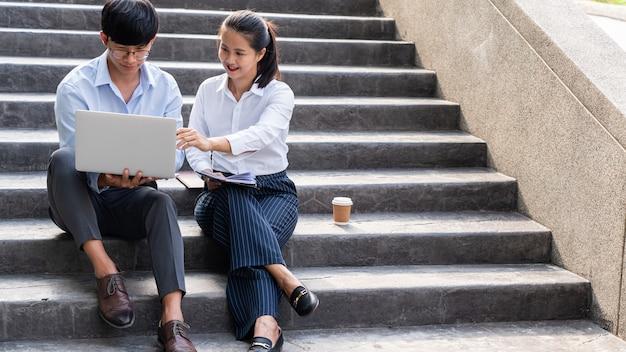 Zwei asiatische geschäftskollegen, die auf einer treppe sitzen, diskutieren und kommentieren die arbeit mit laptop