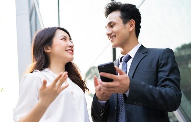 Zwei asiatische geschäftsleute, die smartphone benutzen und zusammen sprechen