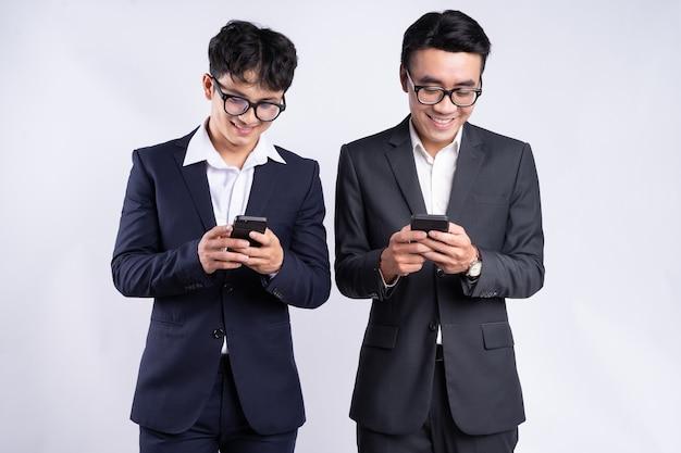 Zwei asiatische geschäftsleute mit smartphone auf weißem hintergrund