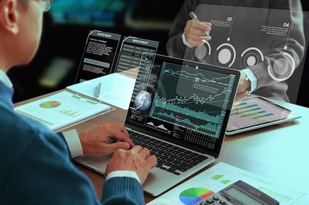 Zwei asiatische geschäftsleute oder analysten in einem modernen büro überprüfen jahresabschlüsse auf die geschäftsleistung und analysieren die kapitalrendite, den roi.