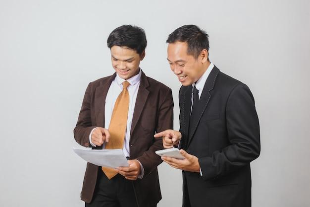 Zwei asiatische geschäftsmann im anzug, der mit einem smartphone lächelt, während er auf einen papierbericht zeigt