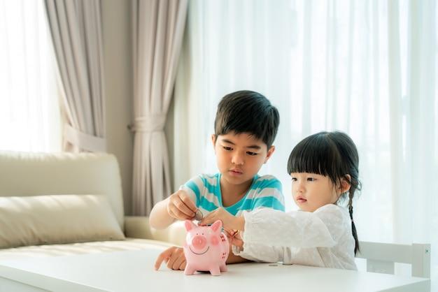 Zwei asiatische geschwister legen zusammen eine münze in ein sparschwein