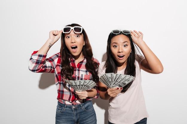 Zwei asiatische hübsche entsetzte nette damen, die geld halten.