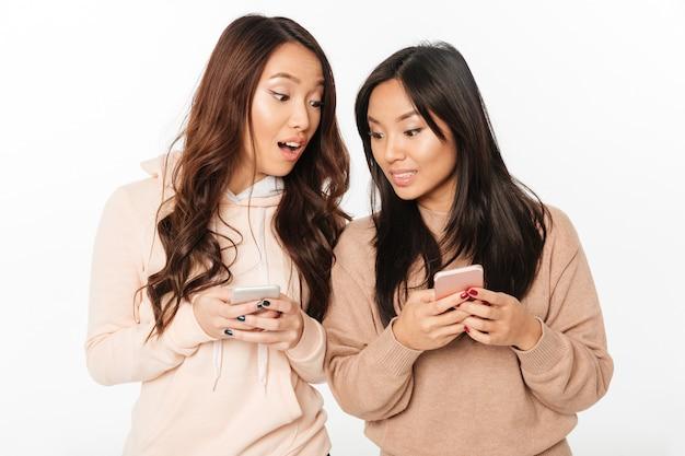 Zwei asiatische hübsche entsetzte positive damenschwestern.