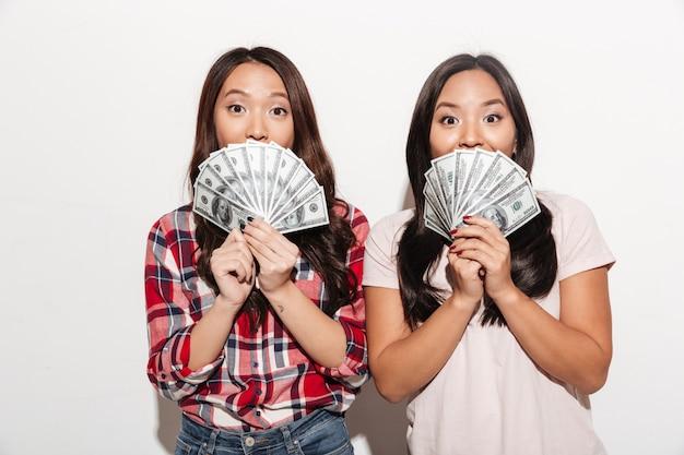 Zwei asiatische hübsche süße damen, die gesichter mit geld bedecken.