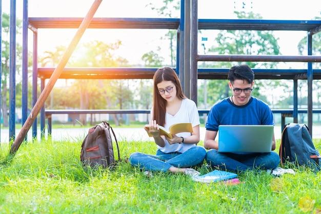 Zwei asiatische junge college-leute, die über lesebuch sich besprechen und laptop verwenden