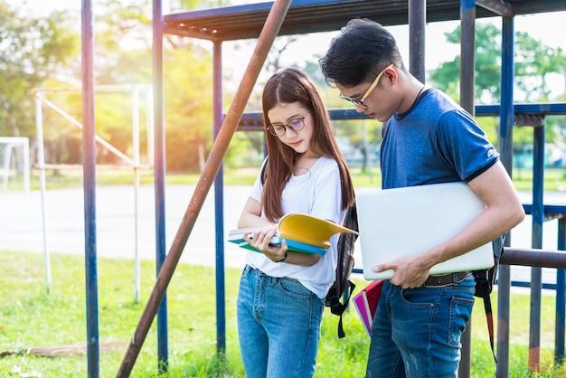 Zwei asiatische junge college-leute, die über lesebuch sich besprechen