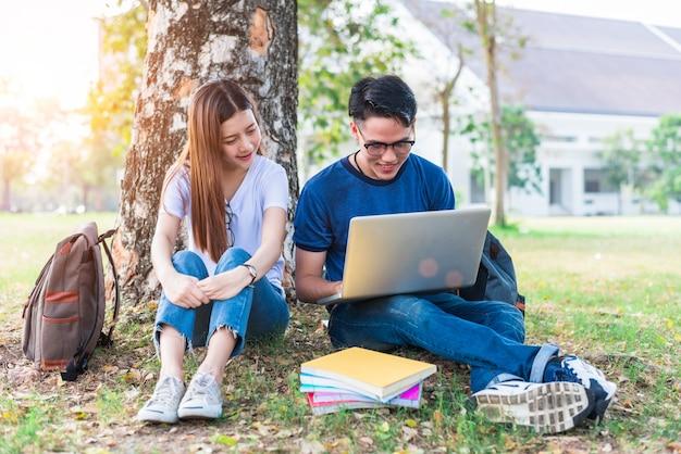 Zwei asiatische junge college-leute diskutieren über hausaufgaben und abschlussprüfung für die prüfung mit laptop