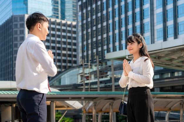Zwei asiatische junge geschäftsmann- und geschäftsfrau-freunde treffen sich in der schrift eines bürogebäudes. anstatt mit einer umarmung oder einem händedruck zu grüßen, zollen sie stattdessen respekt.