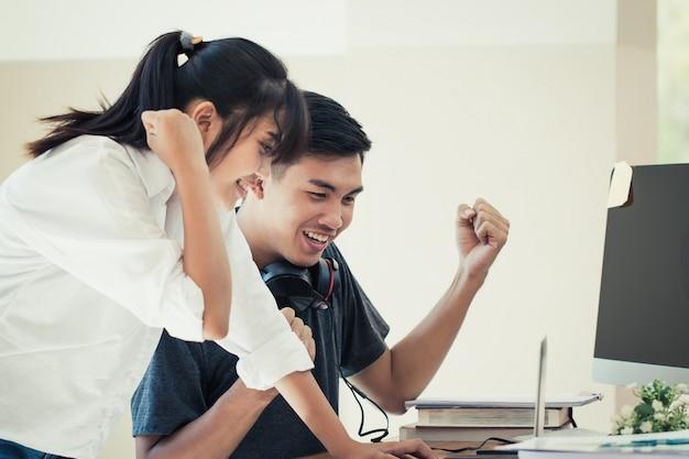 Zwei asiatische junge studenten jugendliche feiern hände hoch und sehen sich die prüfungsergebnisse auf einem laptop an