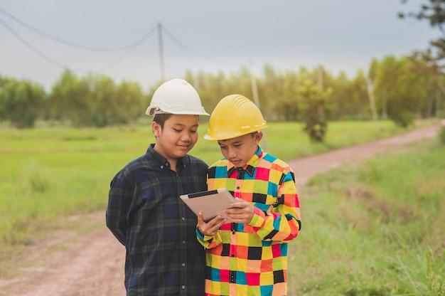 Zwei asiatische jungen tragen einen schutzhelm unter verwendung der tablette, die heraus tür, konzeptingenieur oder vorarbeiter-baukontrolle, bildungscollage-studienschule steht