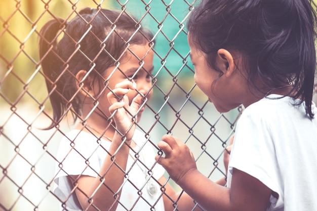 Zwei asiatische kinder, die miteinander sprechen und hand, die stahlmasche im weinlesefarbton hält