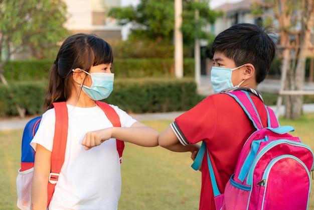 Zwei asiatische kinder im vorschulalter treffen sich im schulpark anstatt mit einer umarmung oder einem händedruck zu grüßen, stoßen sie stattdessen an die ellbogen.