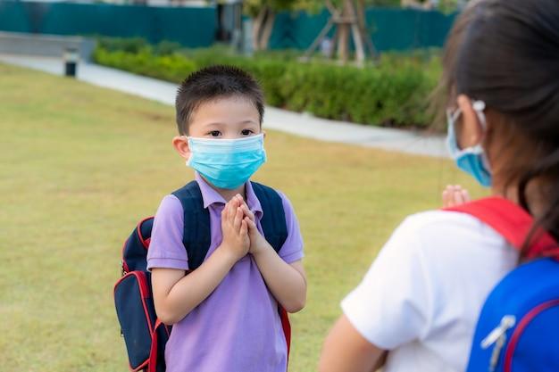 Zwei asiatische kinder im vorschulalter treffen sich im schulpark mit bloßen händen. statt mit einer umarmung oder einem händedruck zu grüßen, zollen sie stattdessen respekt.