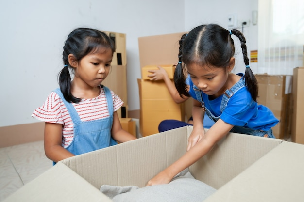 Zwei asiatische kindermädchen, die eltern helfen, am umzugstag sachen in die schachtel zu legen. hausrenovierungs- und umzugskonzept.