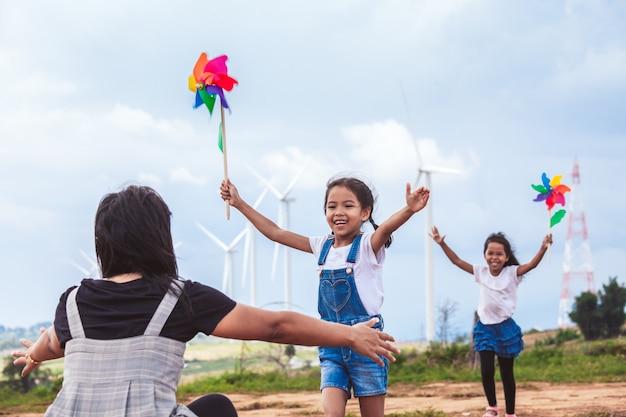 Zwei asiatische kindermädchen, die mit windkraftanlagenspielzeug spielen und zu ihrer mutter laufen, um eine umarmung zu geben