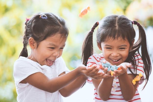 Zwei asiatische kindermädchen, die spaß haben, die süßigkeiten zu fangen, die vom himmel fallen