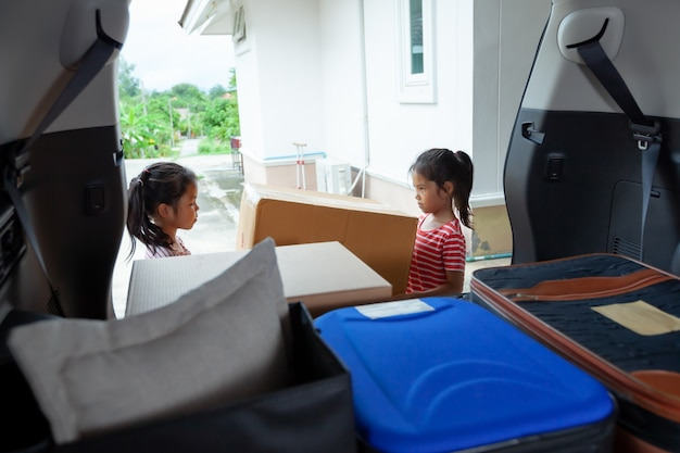 Zwei asiatische kindermädchen helfen eltern, einen karton mit sachen zu tragen, die zusammen ins auto fahren