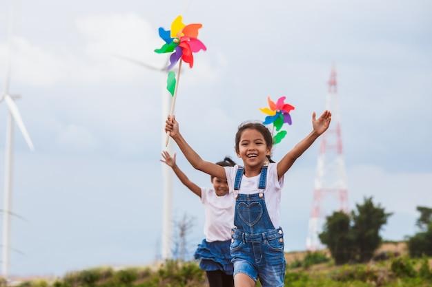 Zwei asiatische kindermädchen laufen und spielen mit windkraftanlagenspielzeug zusammen am windkraftanlagenfeld