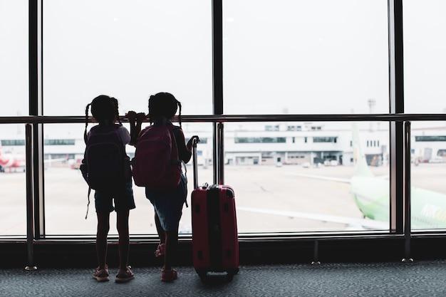 Zwei asiatische kindermädchen mit dem rucksack, der flugzeug betrachtet und auf das verschalen im flughafen wartet