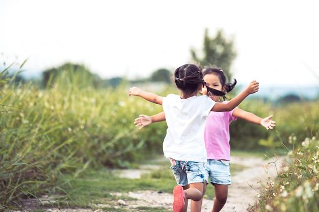 Zwei asiatische kleine mädchen, die laufen, um eine umarmung im weinlesefarbton zu geben