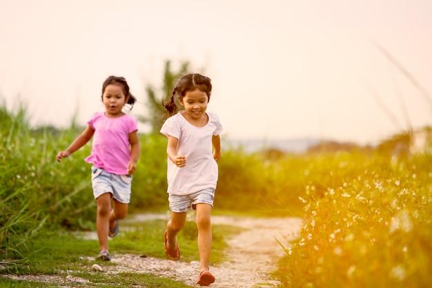 Zwei asiatische kleine mädchen, die spaß haben und zusammen in den park im weinlesefarbton laufen