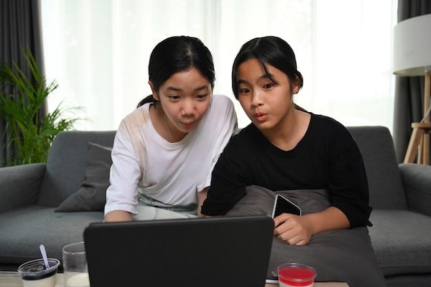 Zwei asiatische mädchen, die auf sofa sitzen und online-cartoons mit digitalem tablet zu hause ansehen