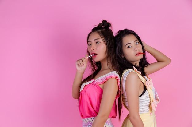 Zwei asiatische mädchen, die freunde sind, sind glücklich und haben ein rosa.