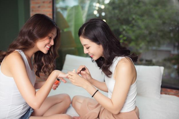 Zwei asiatische mädchen malen zehennägel und fingernägel auf einem bett im wohnzimmer