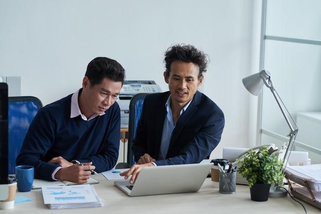 Zwei asiatische männliche kollegen, die zusammen im büro sitzen und laptopschirm betrachten