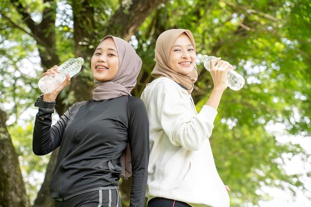 Zwei asiatische muslimische frau mit kopftuch, die eine flasche wasser während des trainings im freien trinkend