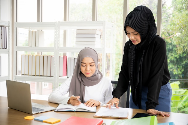Zwei asiatische muslimische geschäftsfrau, die im büro sprechen und zusammenarbeiten