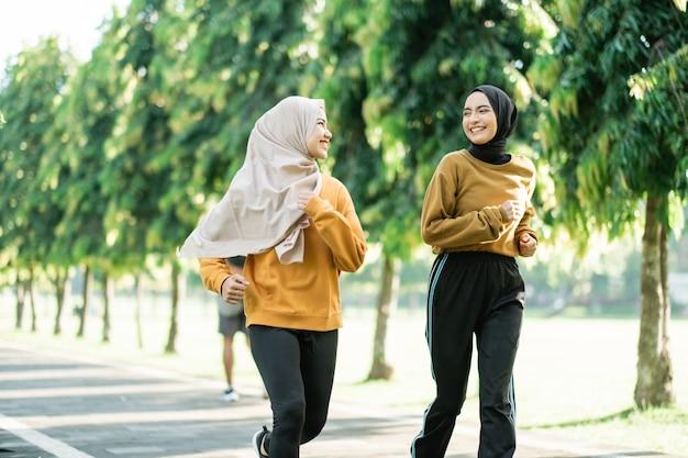 Zwei asiatische muslimische mädchen joggen gerne zusammen, während sie sich am nachmittag auf dem gartenfeld unterhalten