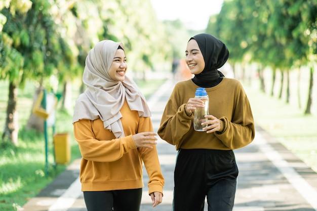 Zwei asiatische muslimische mädchen treiben gemeinsam sport im freien, während sie sich unterhalten und trinkwasser mit einer flasche auf dem parkfeld halten