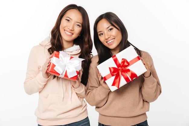 Zwei asiatische nette damenschwestern, die geschenkboxen halten, überraschen.