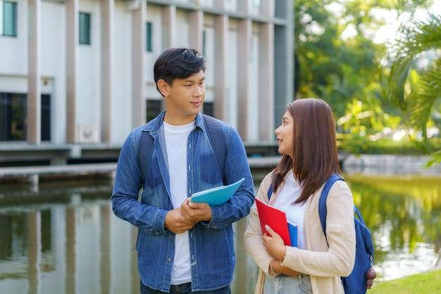 Zwei asiatische paaruniversitätsstudenten, die an einem schönen sonnigen tag im campus gehen und mit klasse im gehweg sprechen.