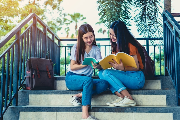 Zwei asiatische schönheitsmädchen, die zusammen bücher für abschlussprüfung lesen und unterrichten